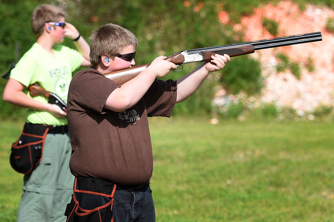 Ethan Kauffman (11) takes aim while his brother Nathan (15) looks on during clay target practice at the Bigfork Gun Club Thursday. (Jeremy Weber/Bigfork Eagle)