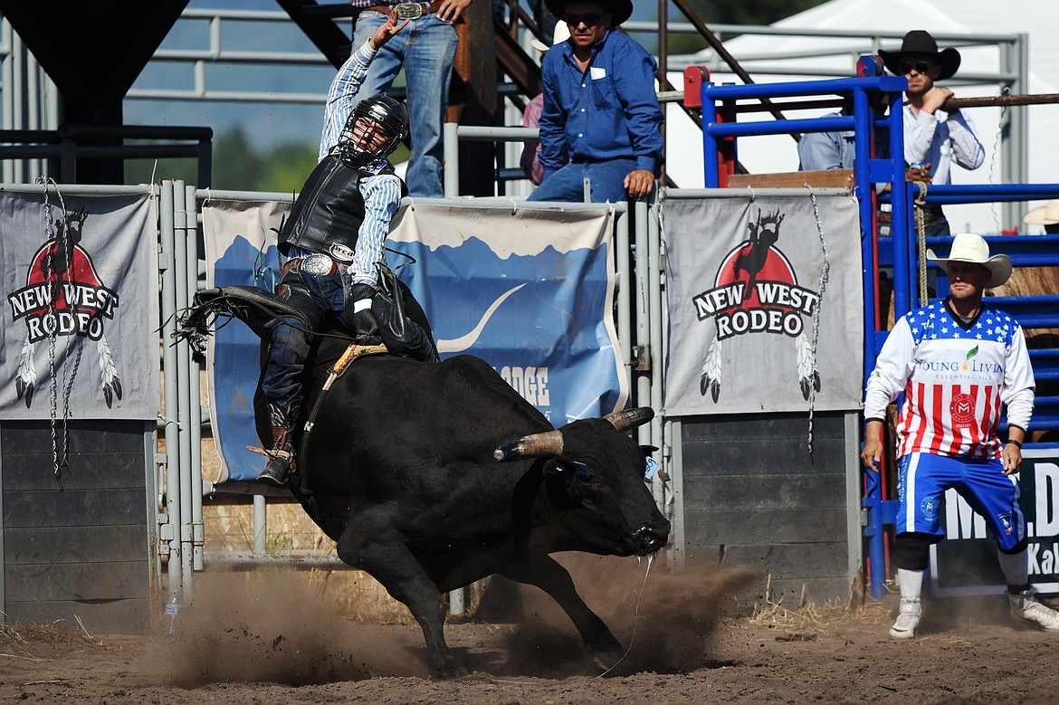 Colby Demo, of Red Bluff, California, holds on to his bull Shaky during bull riding at the Bigfork Rodeo on Saturday, July 4. (Casey Kreider/Daily Inter Lake)