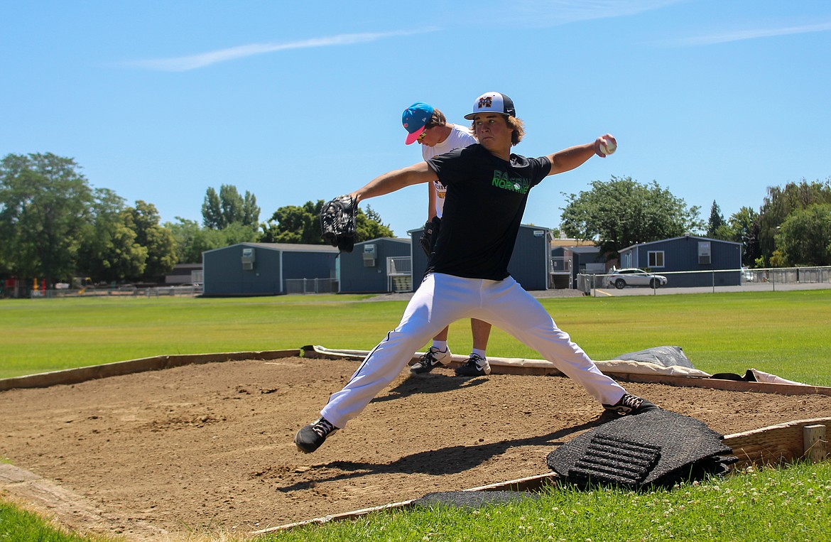 Asher Lindgren, front, fires a pitch during the Columbia Basin Riverdogs practice on Wednesday afternoon in Ephrata, with his brother, Dax Lindgren, getting set for another throw behind him.