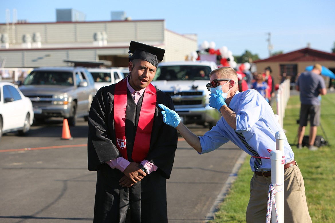 Emry Dinman/Columbia Basin Herald Hoping to keep the crush of students and cars moving and in sync, district staff helped point out where students needed to walk to receive their diploma.
