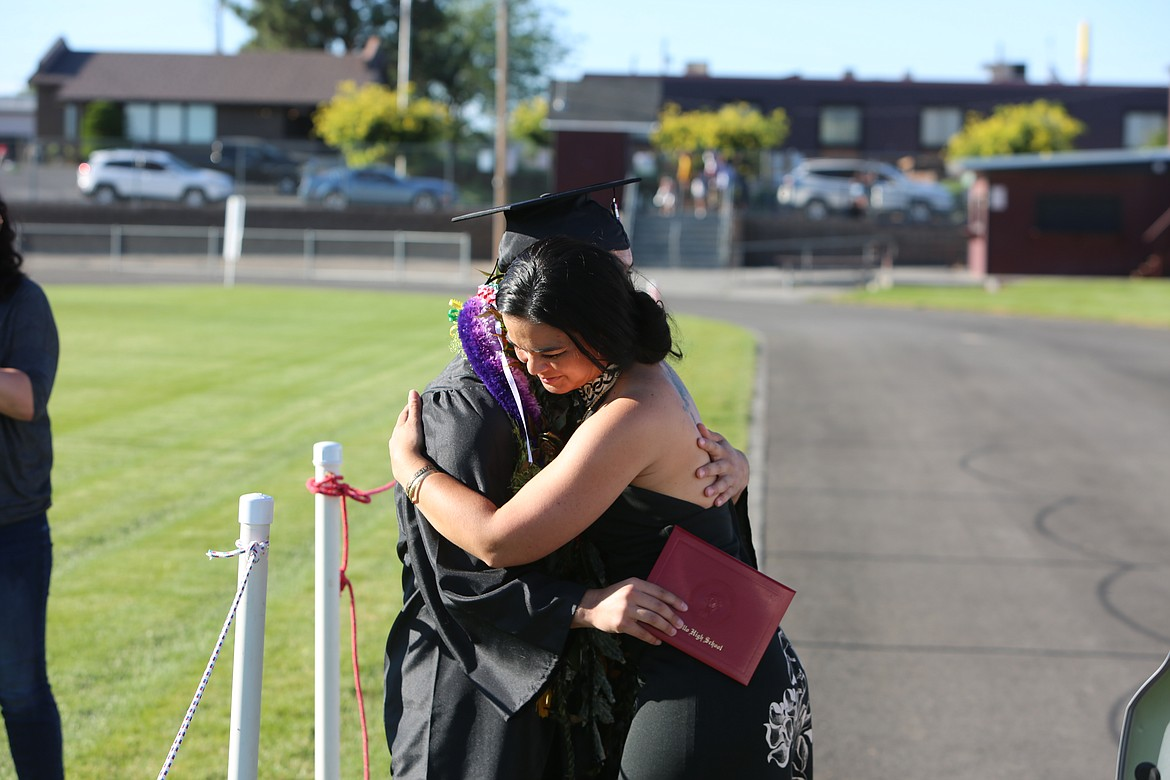 Emry Dinman/Columbia Basin Herald After placing a lei around his neck, a mom and her newly graduated son hug Friday at Othello High School's graduation ceremony.