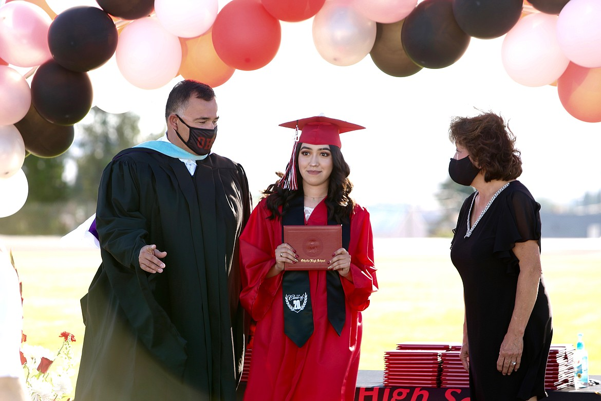 Emry Dinman/Columbia Basin Herald Wreathed by balloons, taking her mask off just long enough to get her photo taken, a newly graduated student holds up her diploma.