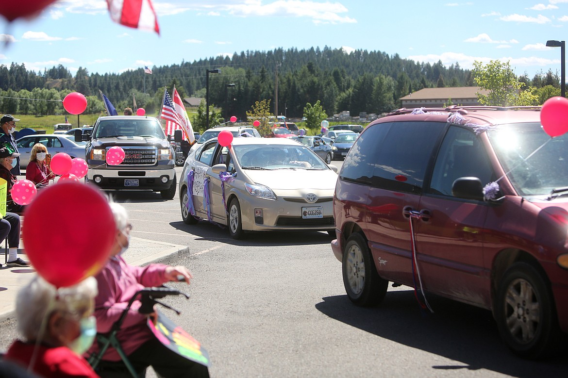 $ID/NormalParagraphStyle:Two dozen cars cruise by Rising Mountains Assisted Living to celebrate resident Harriet Dent's 100th birthday.