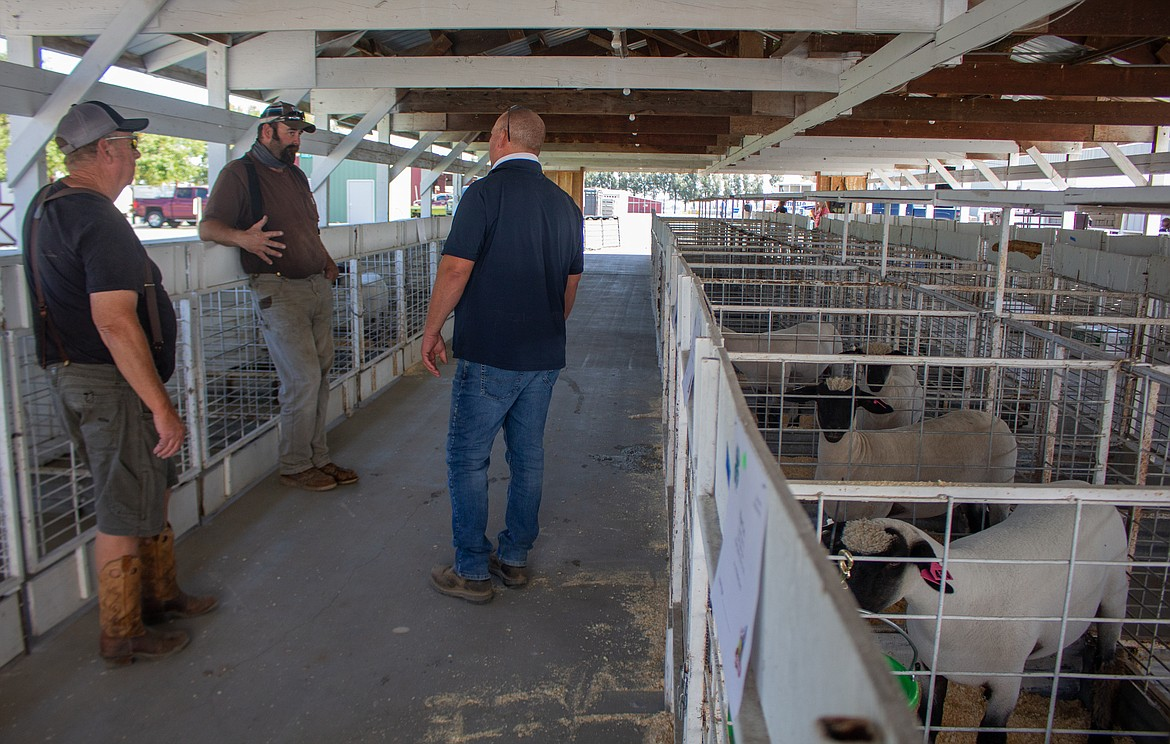 Left to right, Bill Erickson, John Nelson, and Andy Erickson take some time to catch up after dropping off animals for the livestock sale at the Grant County Fairgrounds on Wednesday.