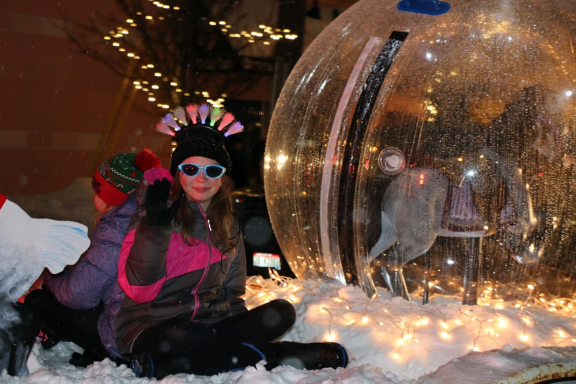 A youngster is decked out in her sparkling, well-lit best winter garb as she waits on the Carousel of Smiles float for the start of the 2019 Winter Carnival Parade.