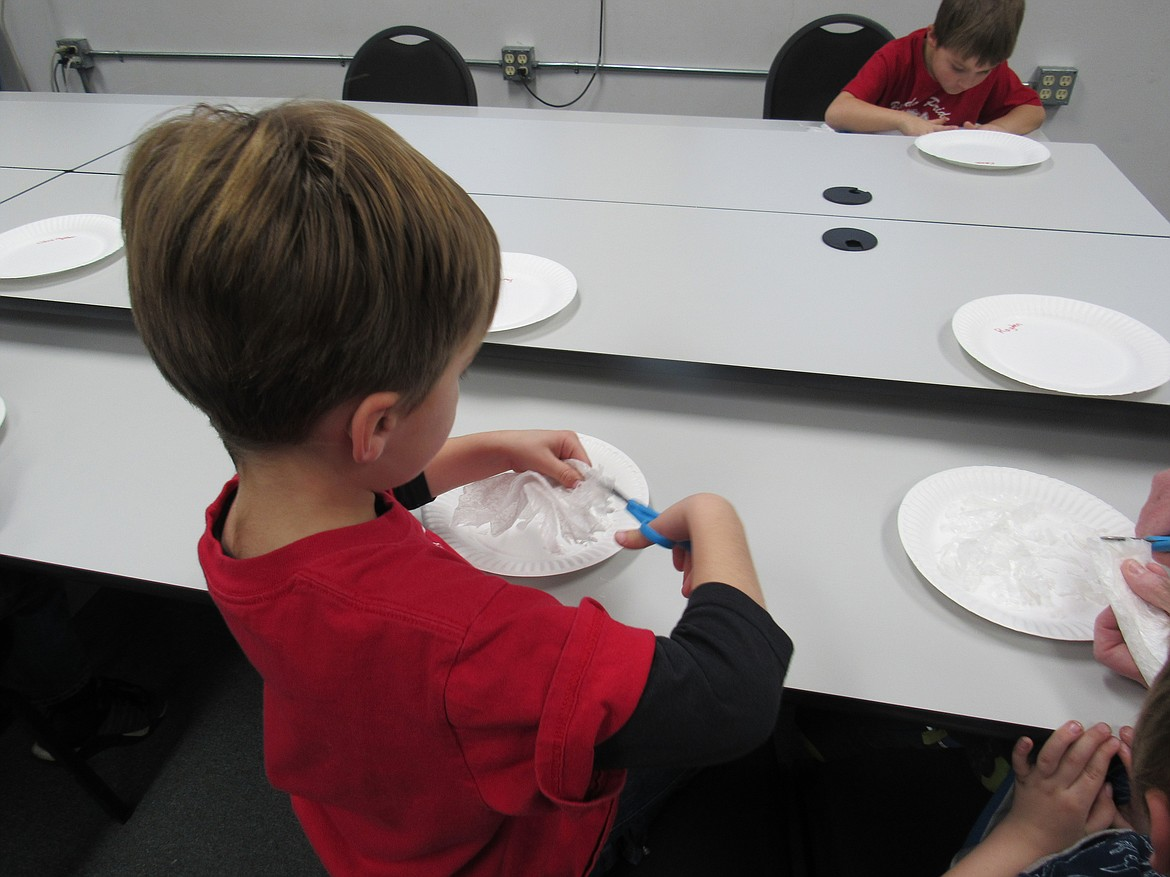 "(Courtesy photo)   An Idaho Hill Elementary kindergartner works on a ""Snow White Mystery Science"" project making snow flakes as part of a STEaM activity at the school recently."