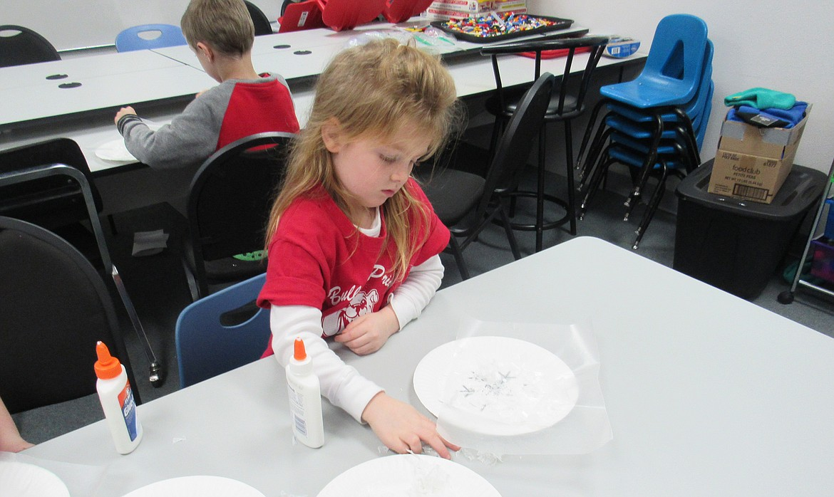 """(Courtesy photo) An Idaho Hill Elementary kindergartner works on a """"Snow White Mystery Science"""" project making snow flakes as part of a STEaM activity at the school recently."""