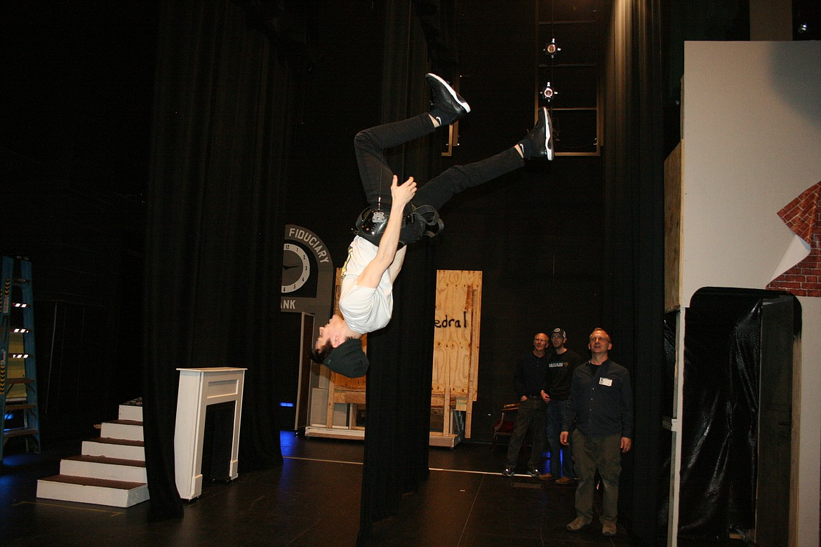 """Taylor Street (upside down) practices flipping through the air. Street plays Bert in the Quincy Valley Allied Arts production of """"Mary Poppins."""""""