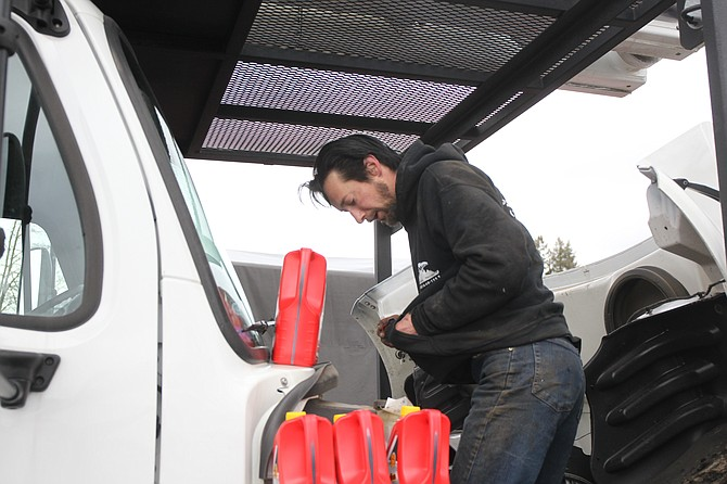 Brian Peirano tries to briefly warm his hands as he maintains a tree service truck during a frigid February day. The eight-year worker at Don Taylor Tree Service said the last winter months are financially some of the hardest for employees and owners alike.