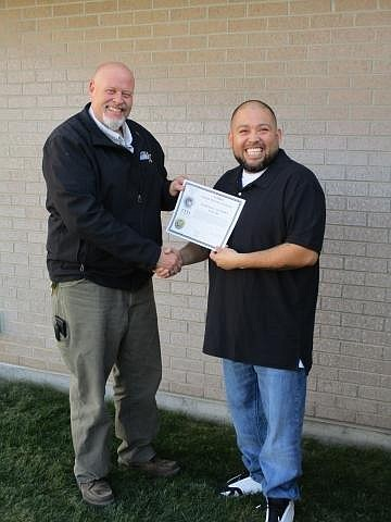 Correctional case manager Craig Leigh presents Rolando Ibarra Jr. with his recertification as an associate electronics technician at the Nampa Re-entry facility in November. Ibarra lost his original certification while serving time in the prison system.