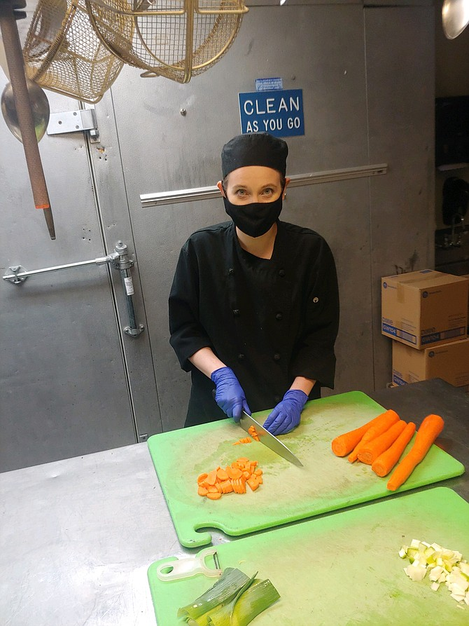 Shelby Stipek of Cedars Floating Restaurant in Coeur d'Alene slices carrots leading up to a long-awaited re-opening. Restaurants are once again able to open their dining areas to patrons after COVID-19 wreaked havoc on the restaurant industry. Now, they hope tourists are willing to return to the table.