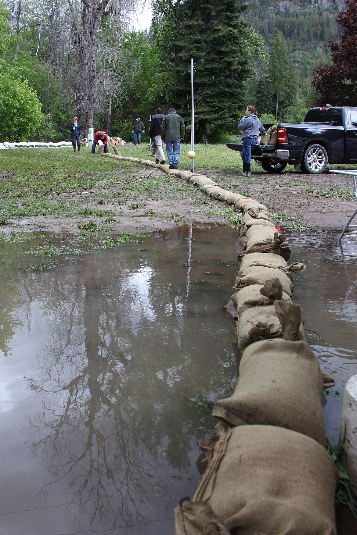 Volunteers tamp down sandbags near Trestle Creek on Thursday afternoon.