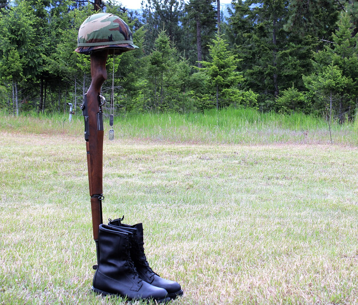 (Photo by TONIA BROOKS)   The fallen soldier battle cross — made up of a rifle stuck into the ground or soldier's boots, with helmet on top, along with dog tags are sometimes placed on the rifle — shows show honor and respect for the dead.