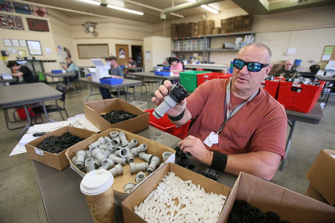 Tesh employee Jeff Shields assists with assembling pieces for cellphone tower surge protectors Monday in the vocational center. Tesh has returned to its normal business hours after six weeks of closure and a few weeks of limited staff. (DEVIN WEEKS/Press)