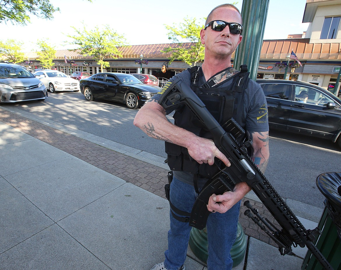 BILL BULEY/Press   Dan Carson stands ready to provide security for downtown Coeur d'Alene businesses on Monday evening.