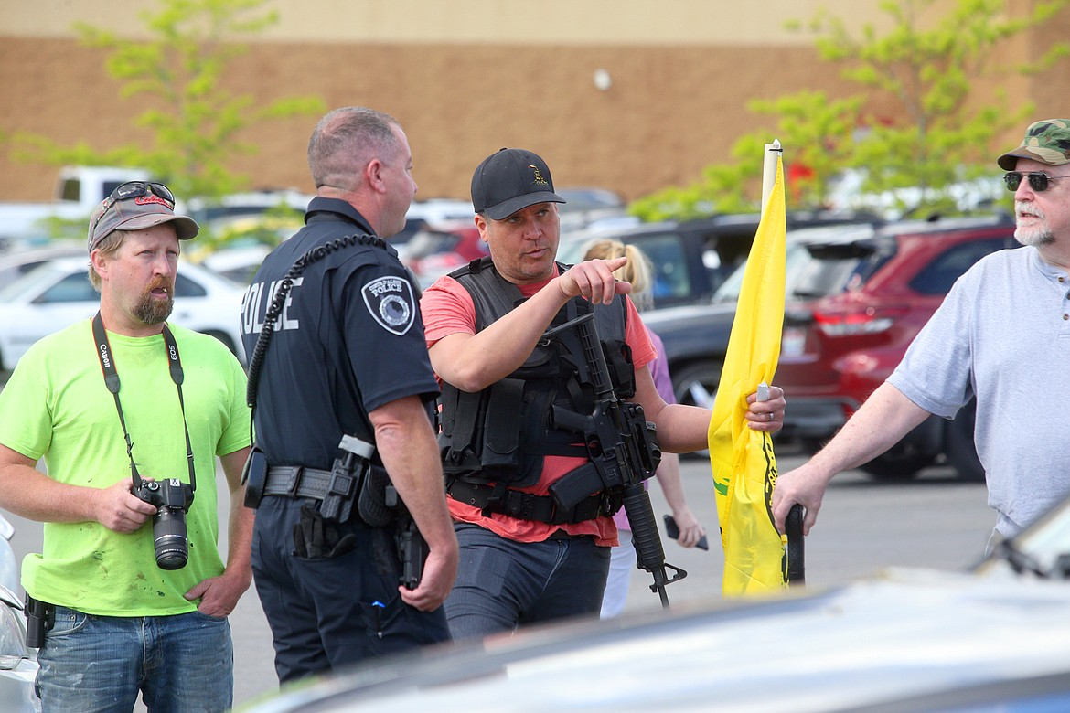 BILL BULEY/Press   Trevor Treller talks to a Coeur d'Alene police officer in the WinCo parking lot on Monday afternoon.