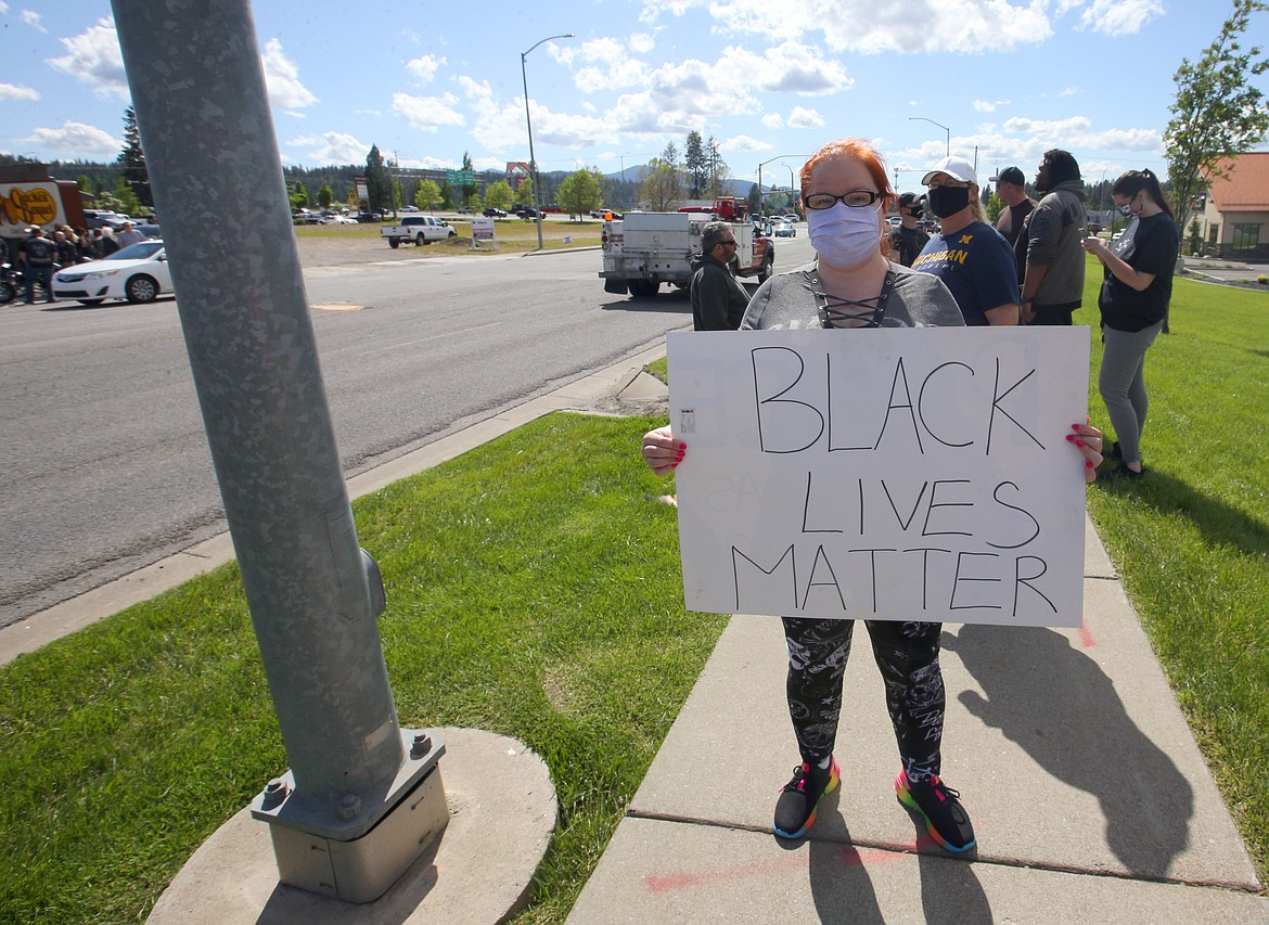 Christy Robinson protests on Appleway Avenue on Monday afternoon.