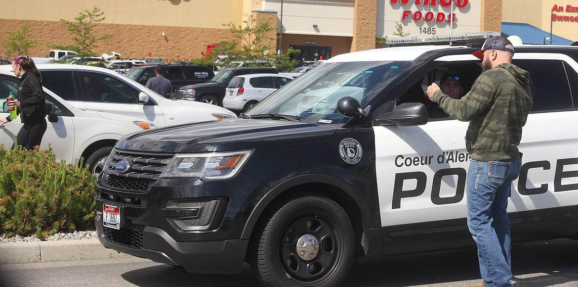 BILL BULEY/Press   A man talks to police outside the WinCo store on Monday afternoon.