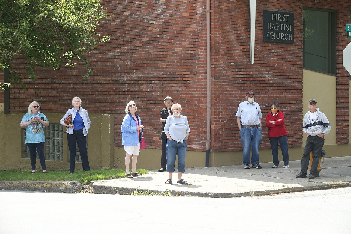 People watch the new cross being put on the steeple at St. Luke's Episcopal Church on Thursday.