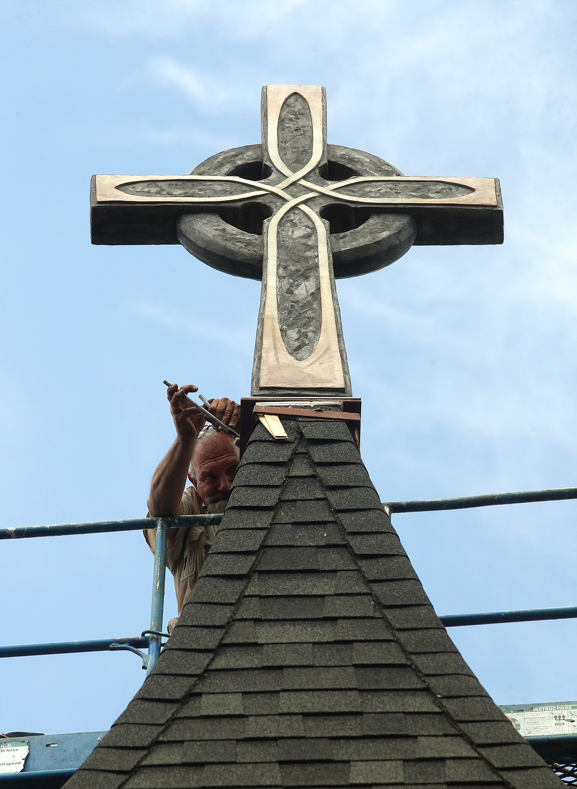 BILL BULEY/Press   David Brooks secures the new cross on the steeple at St. Luke's Episcopal Church on Thursday.