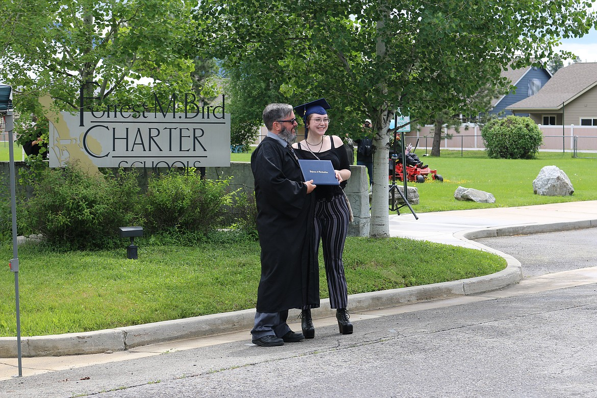(Photo by CAROLINE LOBSINGER)   A Forrest M. Bird Charter School graduates gets her diploma from FBCS School Board Chairman Christopher Warren at Saturday's graduation ceremony at the school.