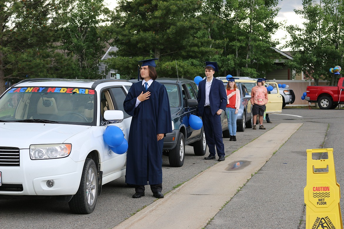 """Forrest M. Bird Charter School graduates stand at the start of Saturday's """"drive-in"""" graduation ceremony at the school. After the ceremony, the school took the fun to the streets as the grads and their families made their way through Sandpoint in a special parade."""