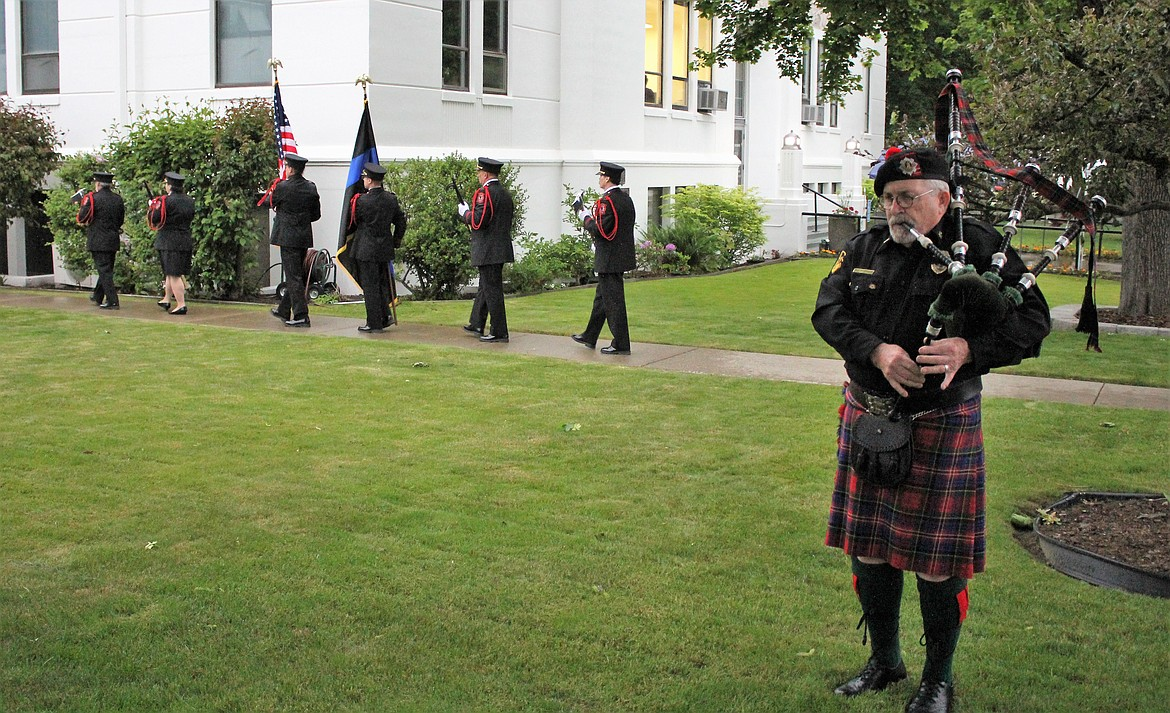 (Photo by TONIA BROOKS) Concluding this year's ceremony was the playing of the pipes by Pat Warkentin, as the Honor Guard walked past the crowd to retire their accoutrements until next time.