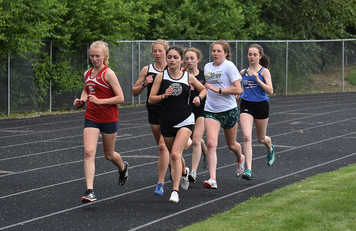 (Photo by DYLAN GREENE)   A pack of runners compete in the girls 1,600 Saturday.