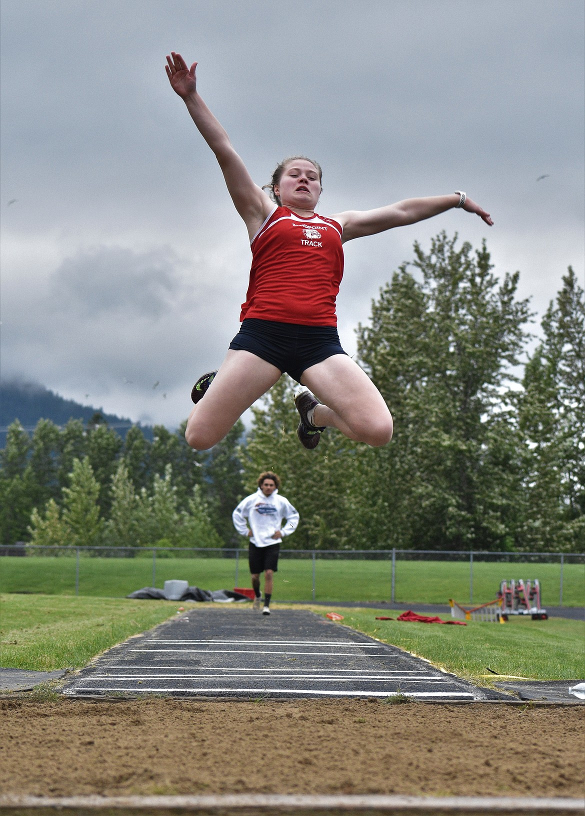 (Photo by DYLAN GREENE)   Senior Maddie Morgan leaps into the pit while competing in the long jump Saturday.