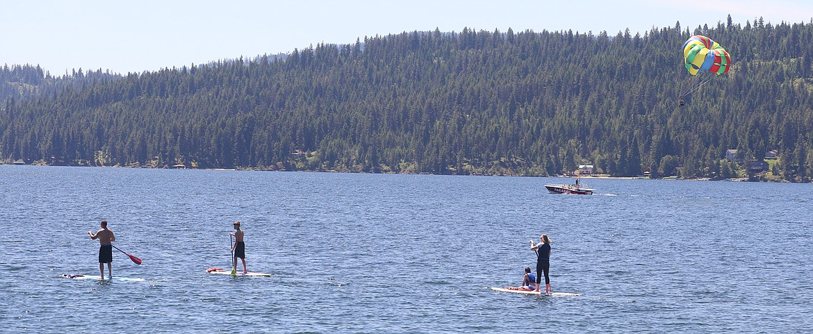BILL BULEY/Press   Paddleboards and a parasailer head out on Lake Coeur d'Alene on Monday.