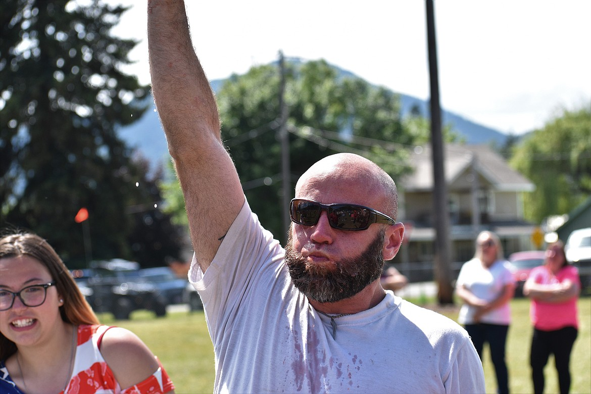 (Photo by DYLAN GREENE)   A man raises his arm to claim the adult title in the watermelon eating contest.