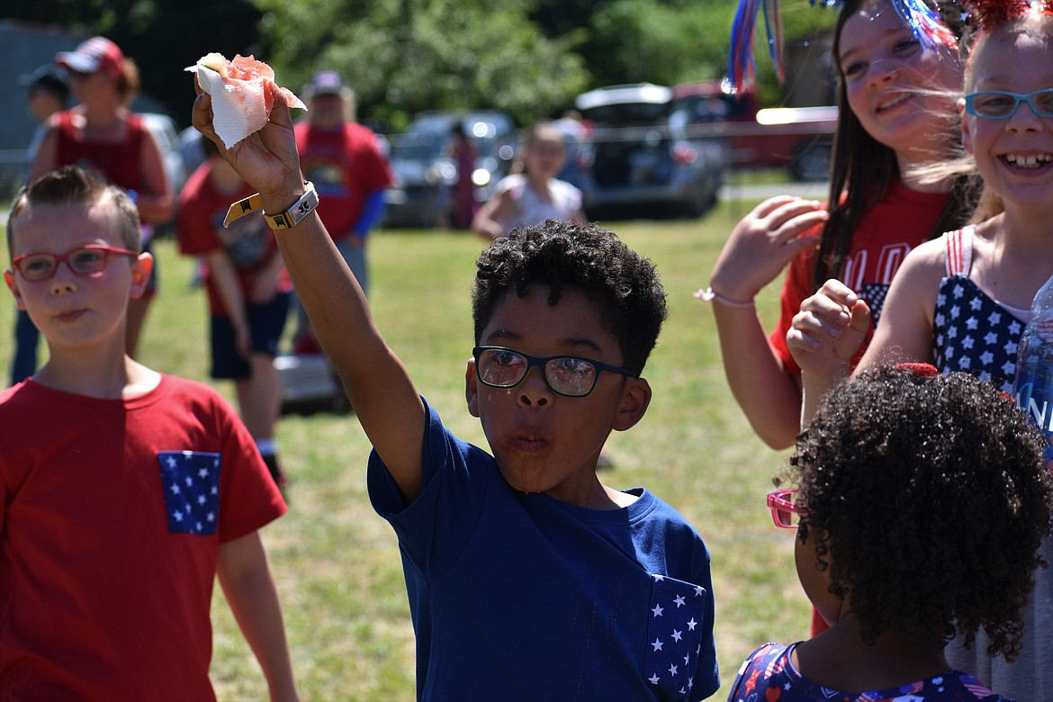 (Photo by DYLAN GREENE)   A young boy raises his arm in the air to claim victory in the Clark Fork watermelon eating contest.