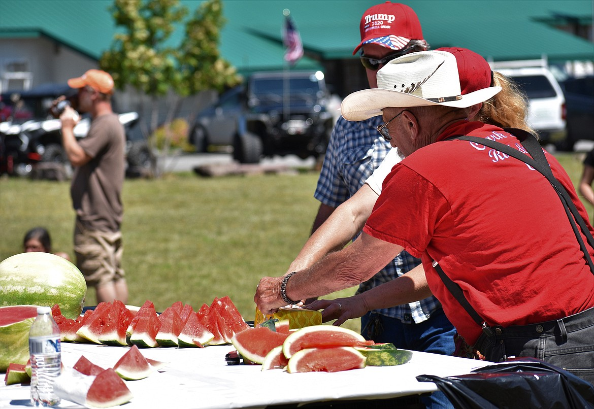 (Photo by DYLAN GREENE)   Volunteers cut up watermelon for the Clark Fork watermelon eating contest.