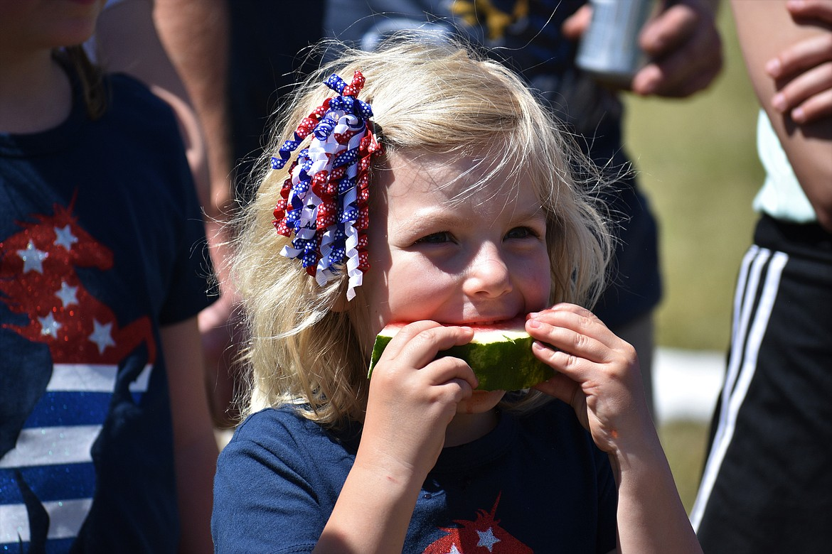 (Photo by DYLAN GREENE)   A youngster bites into a watermelon during the Clark Fork Fourth of July celebration.