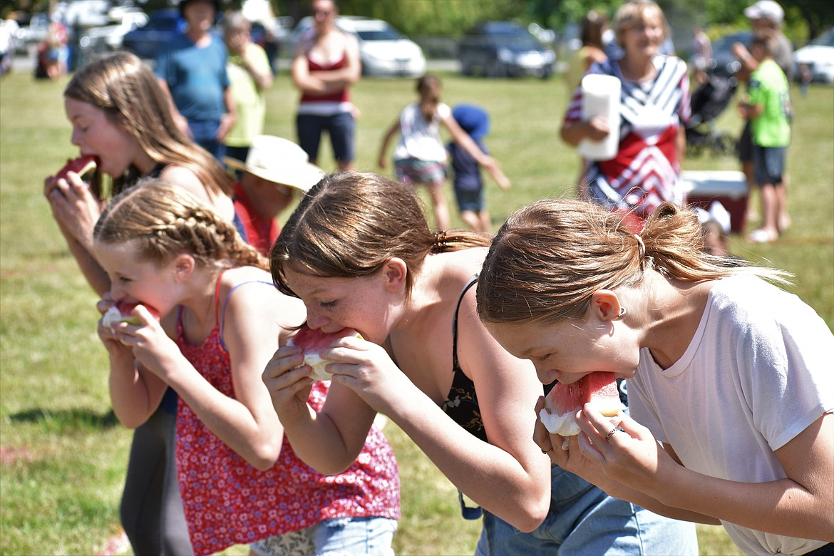 (Photo by DYLAN GREENE)   Youngsters chow down on some watermelon.