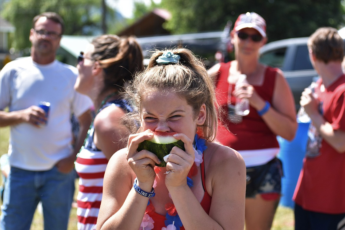 (Photo by DYLAN GREENE)   A teenager takes a big bite out of her watermelon slice.