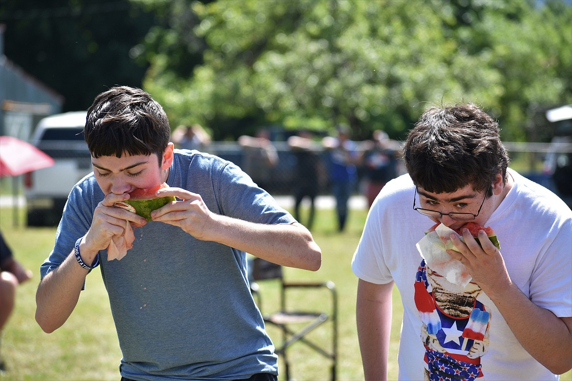 (Photo by DYLAN GREENE)   A pair of teenagers compete to see who can finish their watermelon slice first.