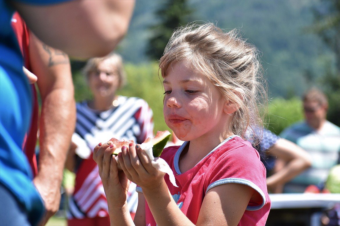 (Photo by DYLAN GREENE)   A youngster looks at how much watermelon she has left to eat.