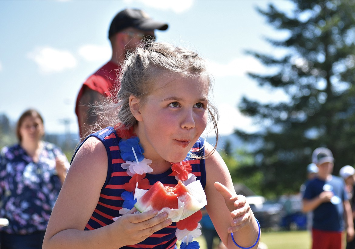 (Photo by DYLAN GREENE)   A young girl releases a smile while trying to hold back from throwing up her watermelon.