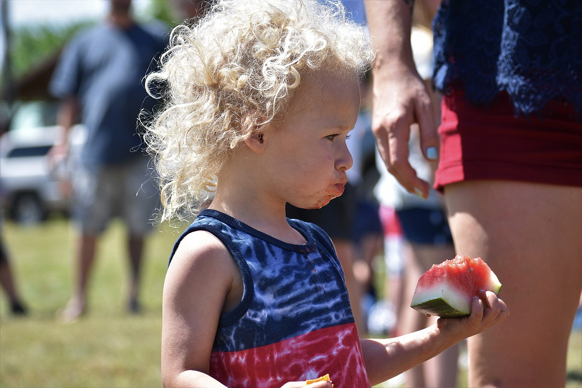 (Photo by DYLAN GREENE)   A youngster holds watermelon in one hand and a cracker in the other.