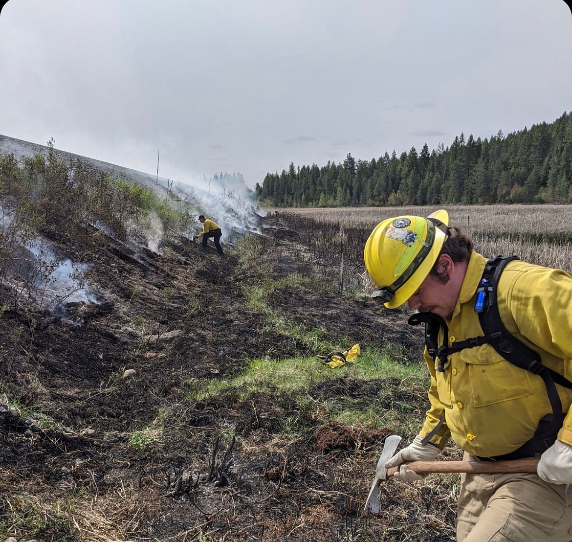Timberlake Fire Protection District Firefighter Jack Duclos, right, works to put out a fire off Kelso Lake Road on May 12. The fire was started by children playing with matches. As fire season heats up in North Idaho, officials ask that people remain cautious and vigilant. A majority of recent fires have been caused by humans. (Photo courtesy of Timberlake Fire)