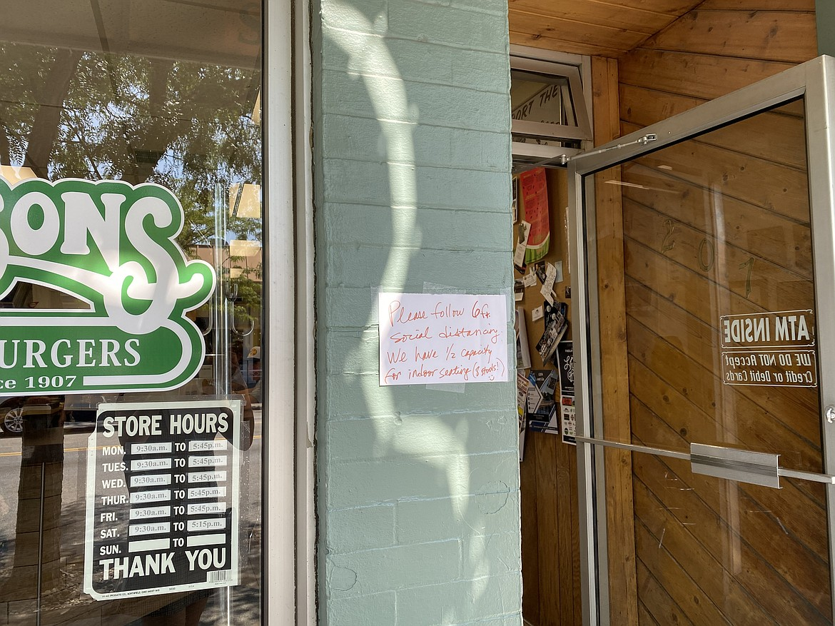 Hudsons Hamburgers encourages patrons to keep their distance while waiting to order with a sign outside the door. (MADISON HARDY/Press)