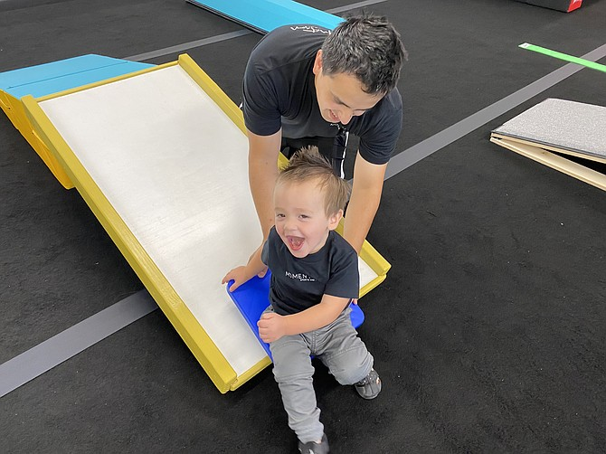 Josh Terra and son Finn test out the ramp slide at Momentum Sports and Play's new center in Coeur d'Alene.