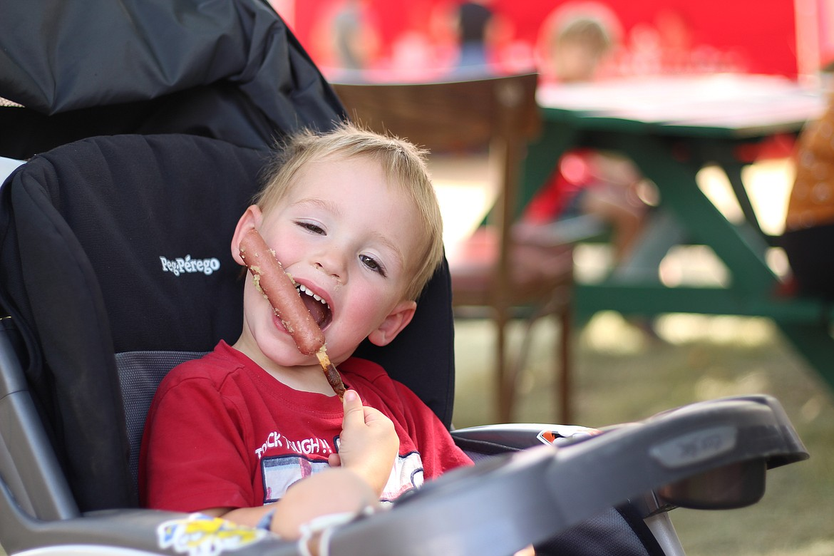 Two-year-old Jacob Dunham of Sandpoint enjoys a corndog at the Bonner County Fair on Friday.