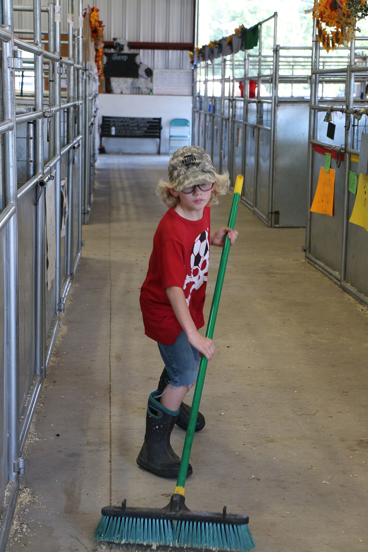 Cole Vanhorn, a member of the Gold 'n' Grouse 4-H Club, works to keep the sheep and goat barn clean at the Bonner County Fair last week.