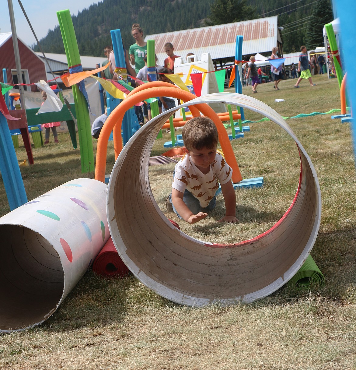 A young fair-goer works his way through an obstacle course at the fair.