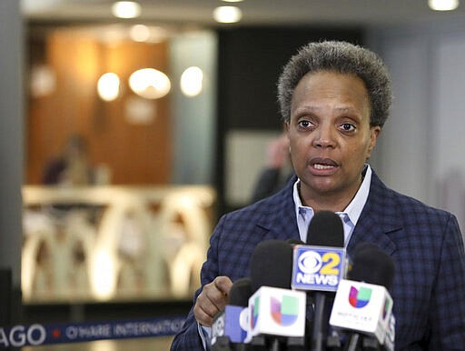 """Chicago Mayor Lori Lightfoot speaks to reporters Sunday, March 15, 2020, at O'Hare International Airport.  Harsh criticism rained on the Trump administration from state and local officials over long lines of returning international passengers at some U.S. airports that could have turned them into coronavirus carriers as they tried to get home. Mayor Lightfoot lambasted the administration for allowing about 3,000 Americans returning from Europe to be stuck for hours inside the customs area at O'Hare International Airport on Saturday, violating federal recommendations that people practice """"social distance."""" (AP Photo/Teresa Crawford)"""