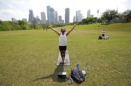 Trey Evans participates in an online yoga class using his laptop and headphones outside at Eleanor Tinsley Park near downtown Houston, Tuesday, March 24, 2020. BIG Power Yoga has been holding online classes during the coronavirus outbreak. A Stay Home - Work Safe Order was issued Tuesday for Houston and Harris County residents to help fight the spread of COVID-19. The order will go into effect at 11:59 p.m. and will last until April 3. Harris County Judge Lina Hidalgo said people should stay home except for essential needs. (AP Photo/David J. Phillip)