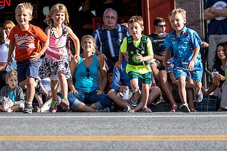 <p>From left, Jax Peterson (4), Ella Peterson (4), Payson Shaw (6) and Nolan Shaw (4) race across Sherman Ave. on Friday evening shortly before the Car d'Lane classic car cruse through downtown.</p>
