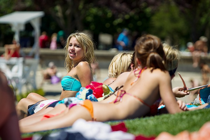 <p>SHAWN GUST/Press Alexis Espies, 19, sits up while sunbathing with a group of girlfriends Wednesday at Independence Point in Coeur d'Alene. Rising temperatures prompted hundreds of beach-goers to gather on the shores of Lake Coeur d'Alene.</p>